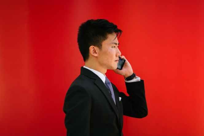 man holding smartphone wearing black notched lapel suit jacket