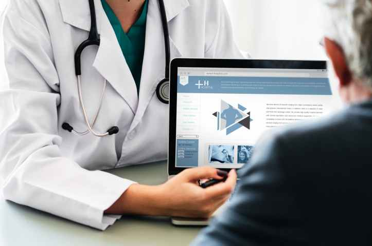 doctor pointing at tablet laptop